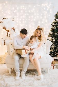Ritratto di bella giovane famiglia sull'albero di natale e sul cotone bianco. genitori attraenti e un figlio piccolo aprono regali di capodanno
