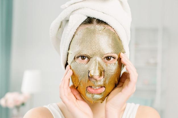 Ritratto di bella giovane femmina in asciugamano bianco sulla testa con foglio cosmetico maschera d'oro sul viso di bellezza. concetto di cura della pelle