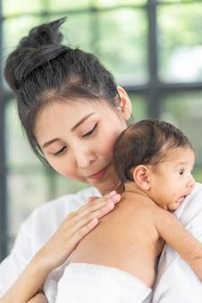 Ritratto di bella madre che gioca con il suo bambino di 1 mese nel letto