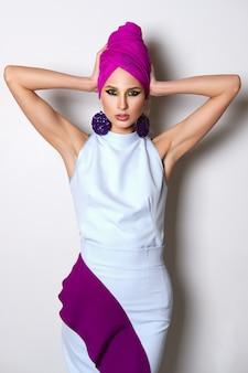 Ritratto di bella modella in abito aderente e turbante sulla testa.