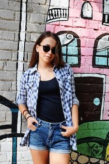 Ritratto di bella ragazza adolescente in occhiali da sole indossati su pantaloncini di jeans e camicia a scacchi, contro un muro con qualche elemento di graffiti.