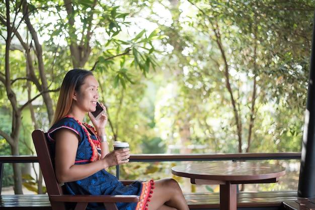 Ritratto di bella ragazza asiatica che utilizza il suo telefono cellulare nella caffetteria.