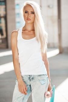 Ritratto di bella ragazza bionda carina in maglietta bianca e jeans in posa all'aperto. ragazza con il pattino blu del penny sulla via