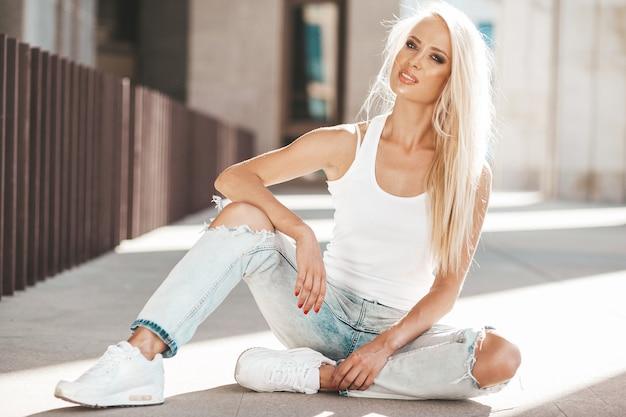 Ritratto di bella ragazza bionda carina in maglietta bianca e jeans in posa all'aperto. ragazza sveglia che si siede sull'asfalto sulla strada