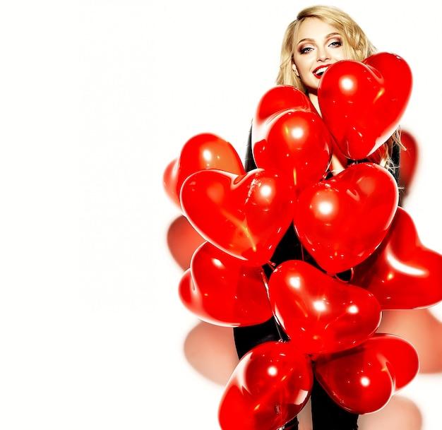 Ritratto di bella ragazza bionda sorridente dolce felice che tiene nelle sue mani palloncini cuore rosso in abiti casual nero hipster