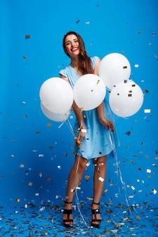 Ritratto di bella ragazza che riposa alla festa sopra la parete blu