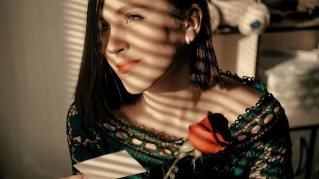 Ritratto di bella ragazza che si siede dalla finestra al tramonto e che guarda sognante fuori dalla finestra