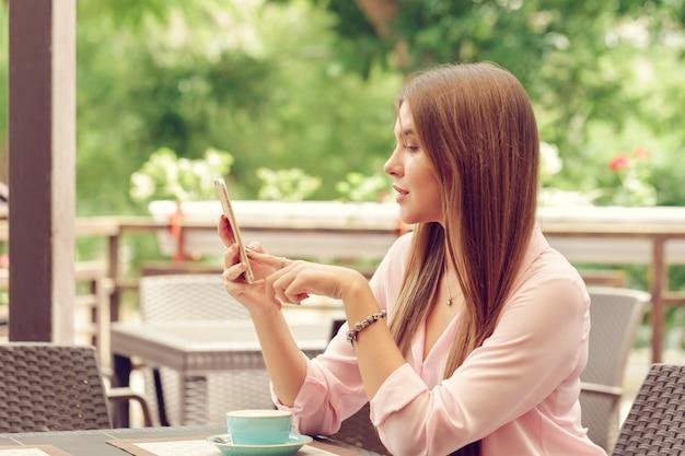 Ritratto di bella ragazza che utilizza il suo telefono cellulare nella caffetteria.