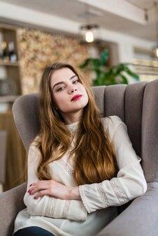 Ritratto di bella ragazza con trucco professionale e acconciatura nel ristorante.