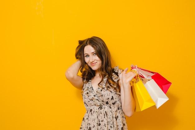 Ritratto di bella ragazza emozionante con gli occhiali da sole che giudicano i sacchetti della spesa isolati sopra giallo
