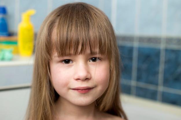 Ritratto di bella ragazza faccia, bambino sorridente con bellissimi occhi e capelli biondi lunghi bagnati