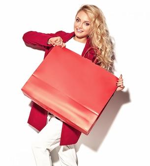 Ritratto di bella ragazza felice felice dolce sorpresa bionda donna con in mano grande borsa della spesa in abiti rossi hipster isolato su bianco