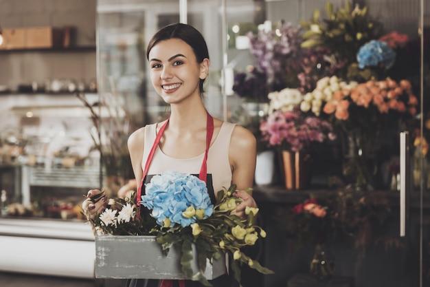 Ritratto di bella ragazza fiorista nel negozio di fiori