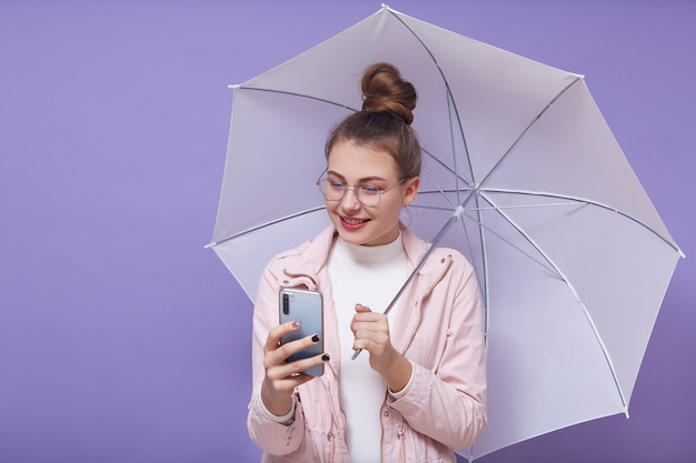 Ritratto di bella ragazza giovane bella con ombrello e smartphone, indossando accessori, facendo selfie, girando video, utilizzando siti di social network, avendo grappolo sulla testa. concetto di gioventù.