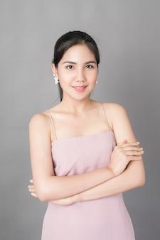 Ritratto di bella ragazza in buona salute in vestito rosa su fondo grigio, colpo dello studio