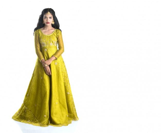 Ritratto di bella ragazza indiana tradizionale che propone sullo spazio bianco.
