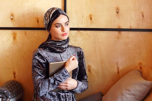 Ritratto di bella ragazza musulmana araba che si siede nella caffetteria con tablet