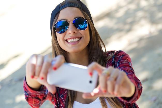 Ritratto di bella ragazza prendendo un selfie con il cellulare in