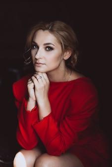 Ritratto di bella ragazza romantica signora in abito rosso nella sala in stile loft. bellezza, moda.