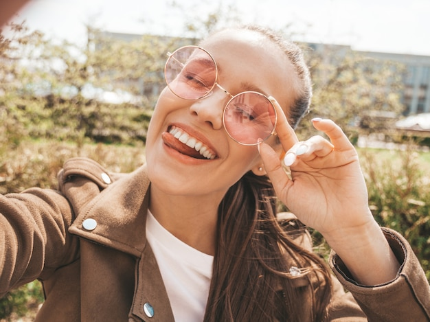 Ritratto di bella ragazza sorridente del brunette in vestiti di giacca e jeans hipster estate