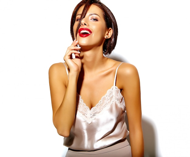Ritratto di bella ragazza sorridente divertente della donna del brunette che impazzisce i vestiti casuali di estate su priorità bassa bianca