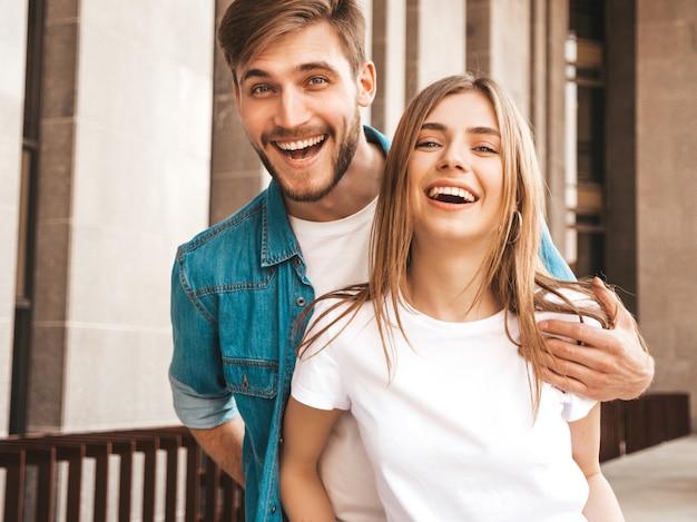 Ritratto di bella ragazza sorridente e il suo bel ragazzo. donna in abiti casual jeans estivi. . abbracciare