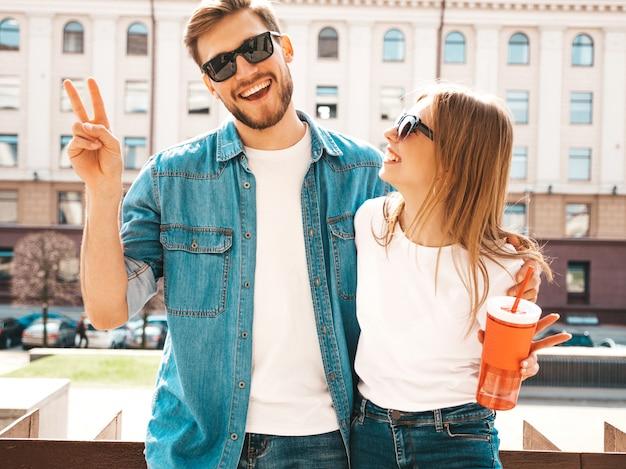 Ritratto di bella ragazza sorridente e il suo bel ragazzo in abiti estivi casual. . con una bottiglia di acqua e paglia