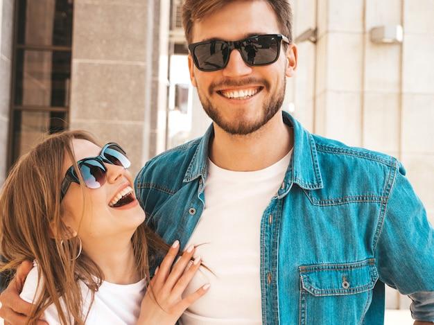 Ritratto di bella ragazza sorridente e il suo bel ragazzo in abiti estivi casual e occhiali da sole. . abbracciare