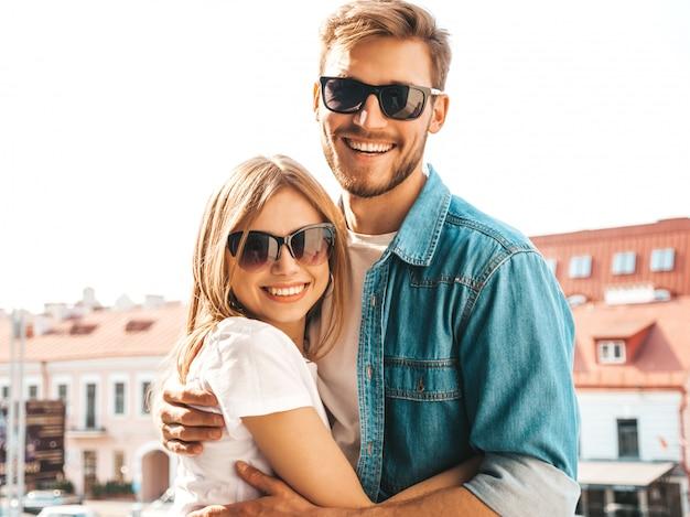 Ritratto di bella ragazza sorridente e il suo bel ragazzo in abiti estivi casual e occhiali da sole.