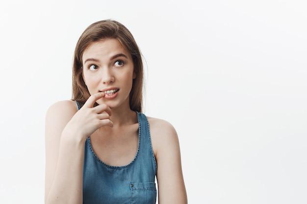 Ritratto di bella ragazza studentessa bruna europea sexy con i capelli lunghi, sorridente, guardando da parte con espressione sognante, tenendo il dito vicino alla bocca
