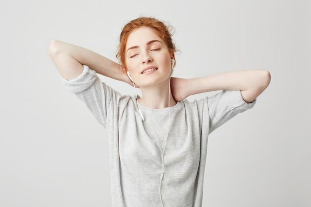 Ritratto di bella ragazza tenera di redhead che ascolta la musica in cuffie con godere sorridente degli occhi chiusi. mani dietro la testa.