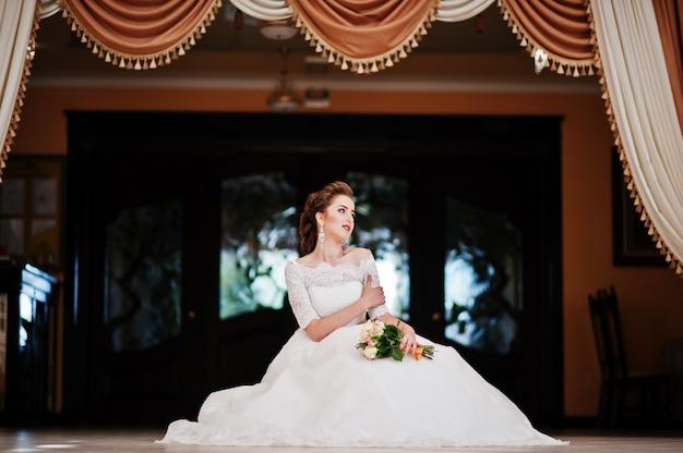 Ritratto di bella sposa alle tende del fondo della sala per matrimoni