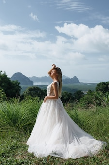 Ritratto di bella sposa bionda in un abito da sposa all'aperto in estate.
