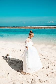 Ritratto di bella sposa che balla sulla spiaggia dietro cielo blu e mare