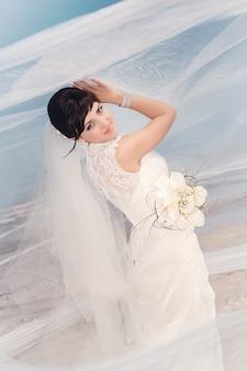 Ritratto di bella sposa che fa una pausa la spiaggia