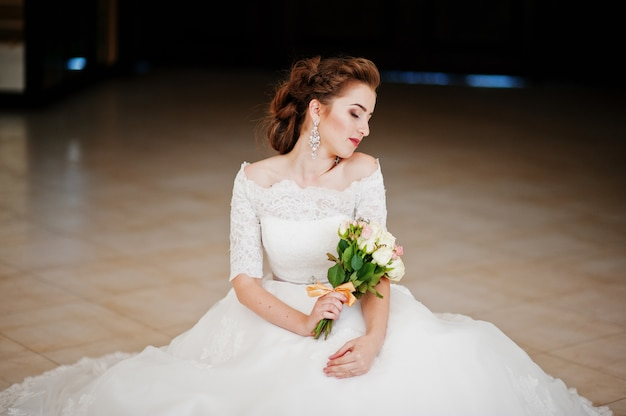 Ritratto di bella sposa che si siede con il mazzo di nozze alla sala per matrimoni