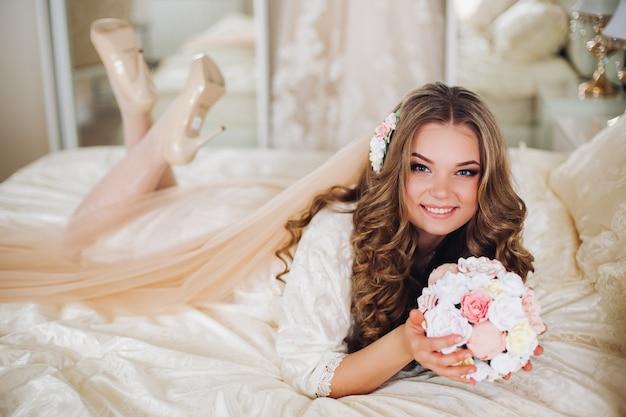 Ritratto di bella sposa con i capelli lunghi in lingerie bianca guardando la telecamera, sorridente.
