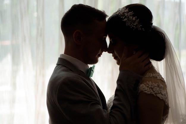 Ritratto di bella sposa e lo sposo contro una finestra al chiuso