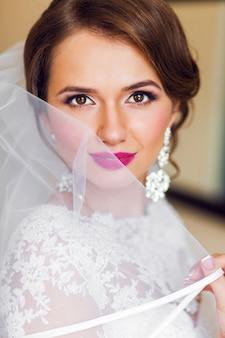 Ritratto di bella sposa in abito da sposa bianco luminoso compongono.