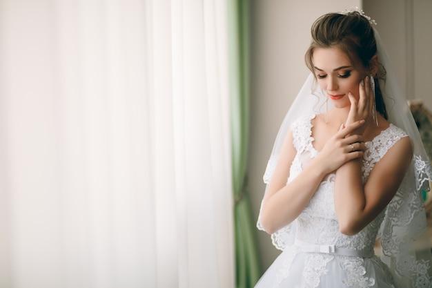 Ritratto di bella sposa in vestaglia di seta bianca con l'acconciatura riccia e il velo lungo che sta finestra vicina in camera da letto, spazio della copia