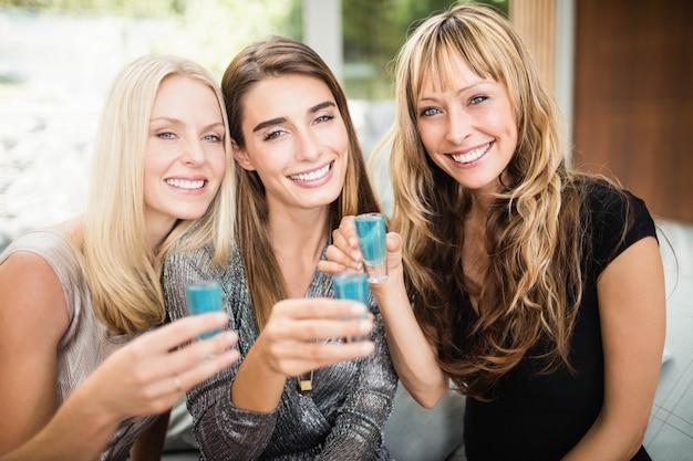 Ritratto di belle donne che sorridono e che bevono bevande alla festa