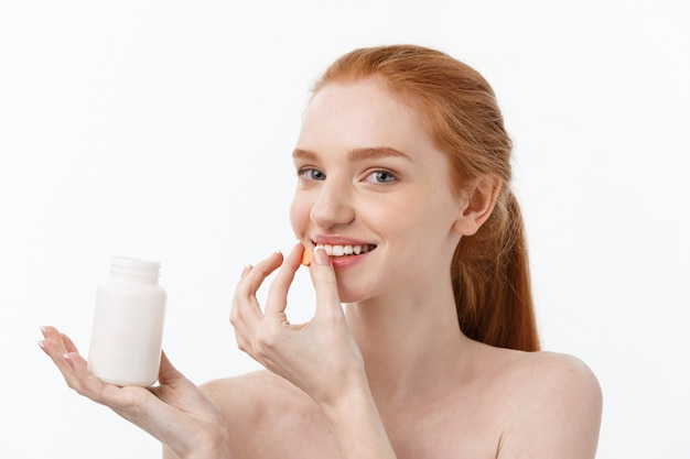 Ritratto di belle pillole caucasiche della tenuta della giovane donna, provanti a prendersi cura del sistema immunitario e della salute sopra grey