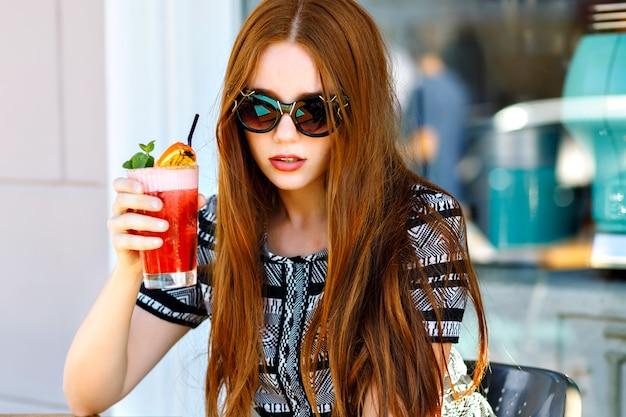 Ritratto di bellezza alla moda all'aperto di signora elegante glamour, capelli lunghi incredibili, abito vintage di lusso e occhiali da sole a occhi di gatto, bere gustosi cocktail freddi, terrazza del caffè della città, viaggi, gioia, relax.