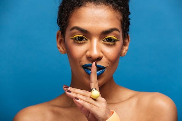 Ritratto di bellezza del primo piano della donna afroamericana stupefacente con trucco di modo che chiede di mantenere silenzio o segreto mettendo il dito sulle labbra isolate, sopra la parete blu