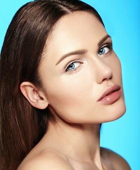 Ritratto di bellezza del primo piano di fascino di bello modello caucasico sensuale della giovane donna con trucco nudo con pelle pulita perfetta isolata su fondo blu