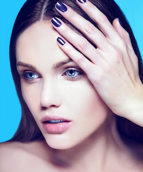 Ritratto di bellezza del primo piano look.glamor di alta moda di bello modello sensuale caucasico della giovane donna con trucco nudo con pelle pulita perfetta su fondo blu