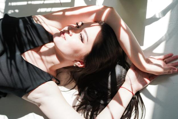 Ritratto di bellezza del volto femminile con la pelle naturale, donna che risiede in biancheria intima nera
