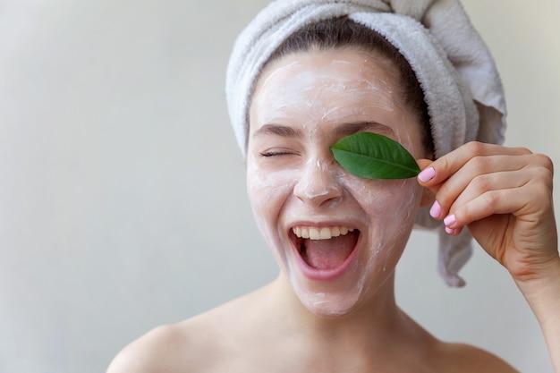 Ritratto di bellezza della donna con maschera nutriente bianca o crema sul viso e foglia verde in mano