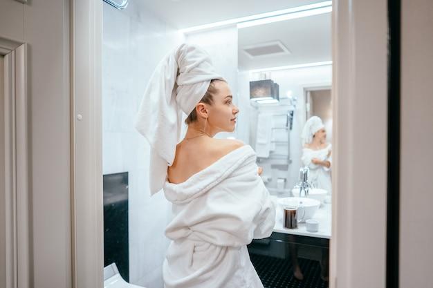 Ritratto di bellezza della donna graziosa che veste un asciugamano di bagno bianco