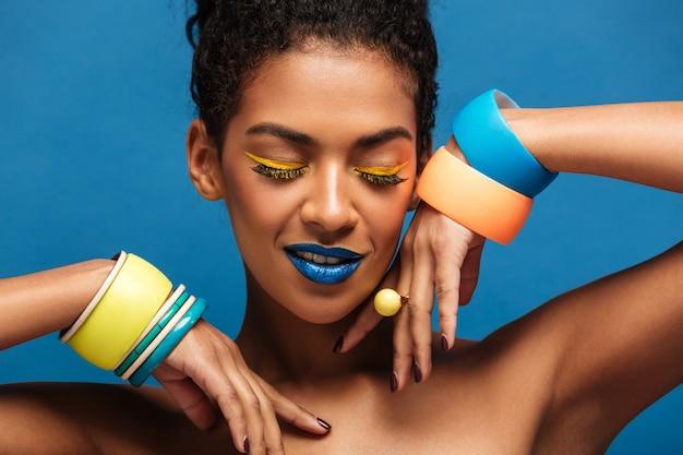 Ritratto di bellezza della giovane donna afroamericana attraente con trucco e braccialetti di modo sulla posa delle mani isolata, sopra la parete blu